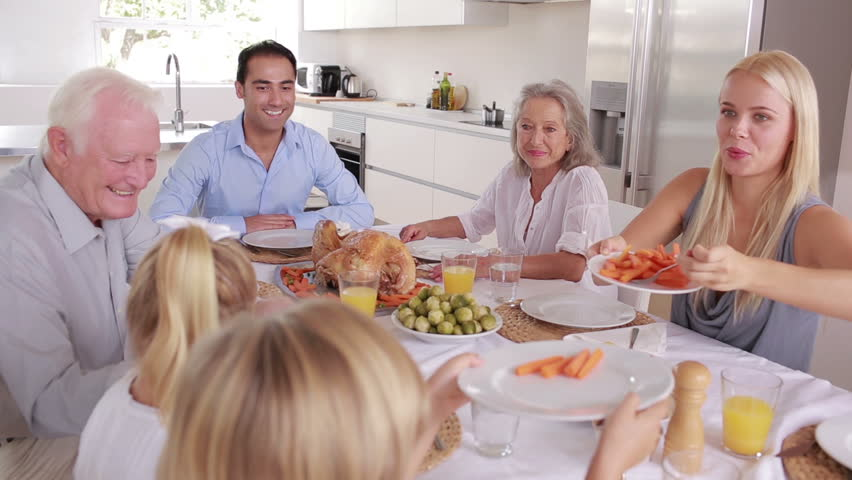 Happy mother serving carrots to son at family dinner in kitchen