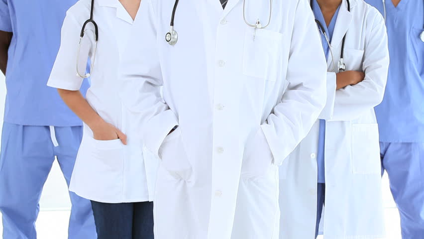 Happy medical team placing their hands in their pockets in a bright room - HD stock footage clip