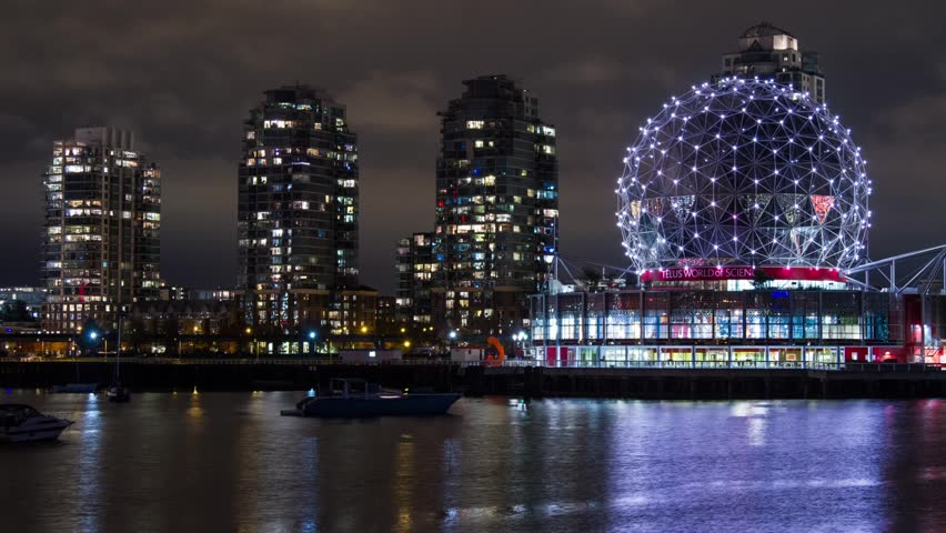 VANCOUVER - CIRCA 2012: Time lapse of a cloudy night across from the illuminated Science World with apartment buildings behind and Skytrain coming in and out behind it circa 2012 in Vancouver, Canada.