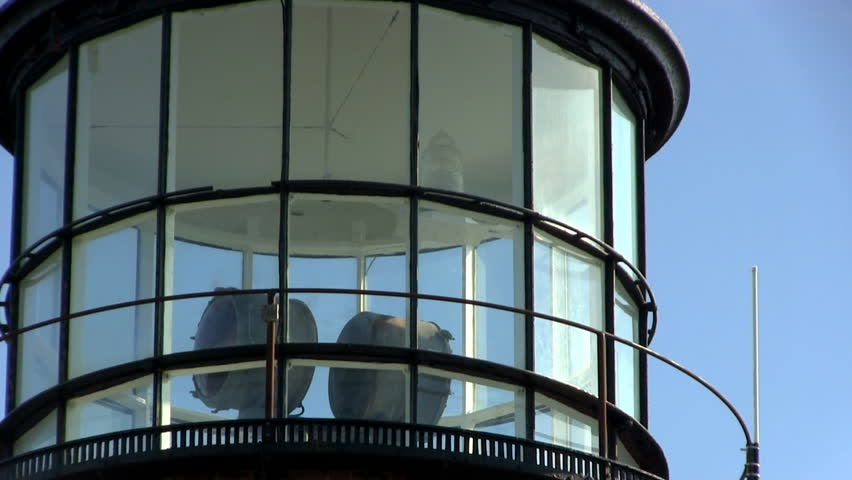 Close-up of lighthouse at Gay Head Aquinnah on Martha's Vineyard with rotating red and white lights behind glass against blue sky  - HD stock video clip