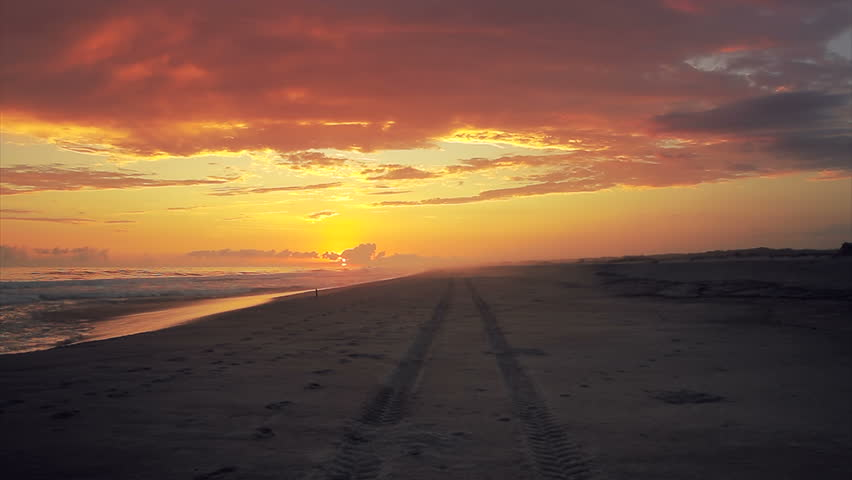 Silhouette of newlyweds on honeymoon walking on the seashore