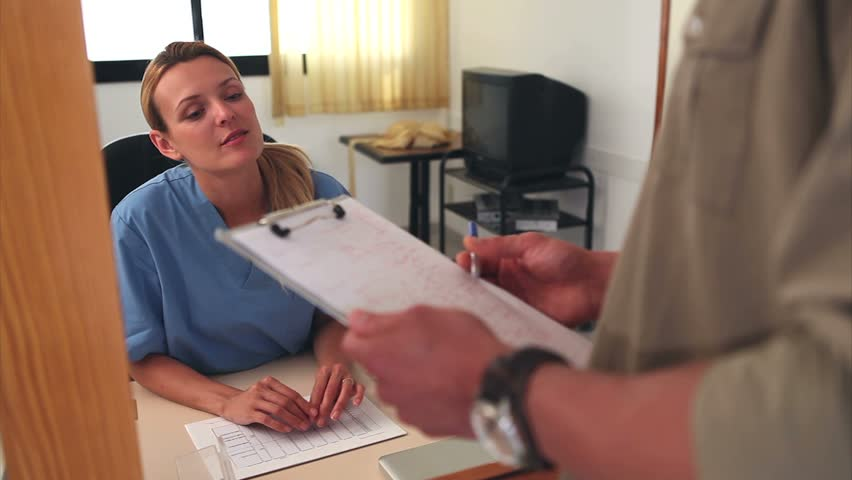 Nurse asking the signature of a patient at a hospital reception - HD stock footage clip