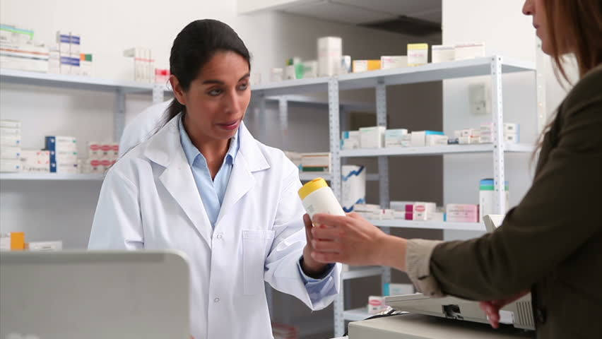 Smiling female pharmacist handing drugs to a customer in a hospital