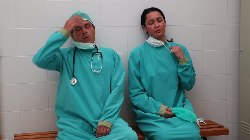 Video of a depressed surgical team sitting on a bench in locker room - HD stock footage clip