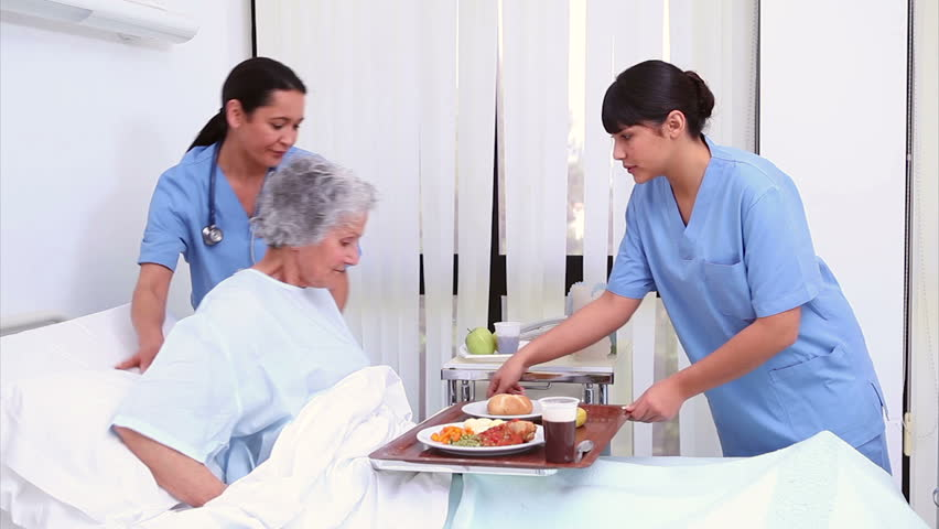 Nurse bringing food to a senior patient in a hospital room - HD stock footage clip