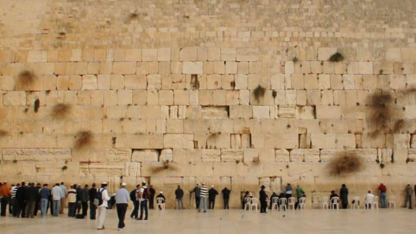 Wide shot. People praying at he Western Wall of Jerusalem.