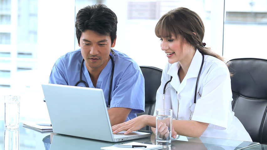 Doctor pointing at the screen of a laptop with a colleague in a bright room - HD stock footage clip