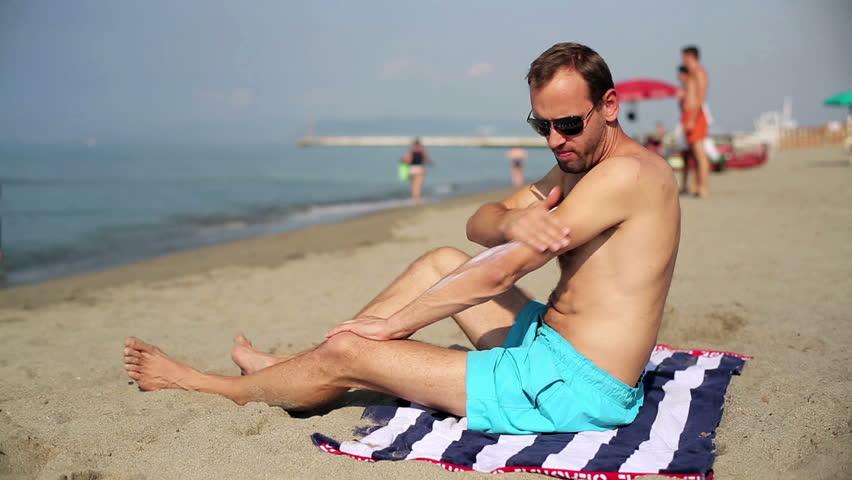 Man applying sun block lotion on the beach  - HD stock footage clip