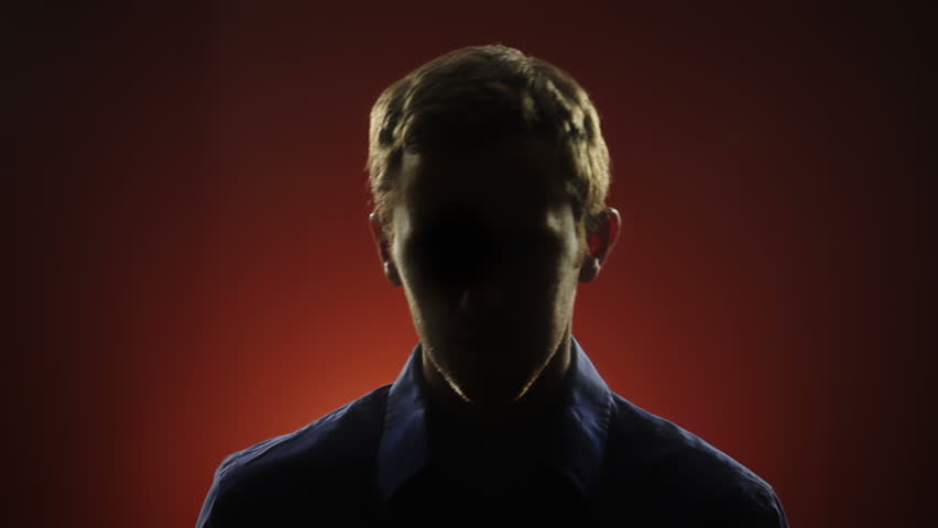 A businessman, whose face is hidden in shadow, stares into the camera in front of a red background. Off-centered version also available.