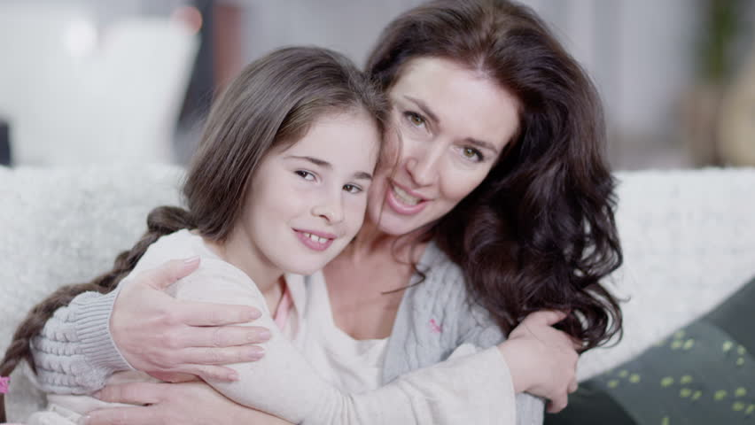 A soft and feminine close up of mother and daughter looking directly into camera. In slow motion.