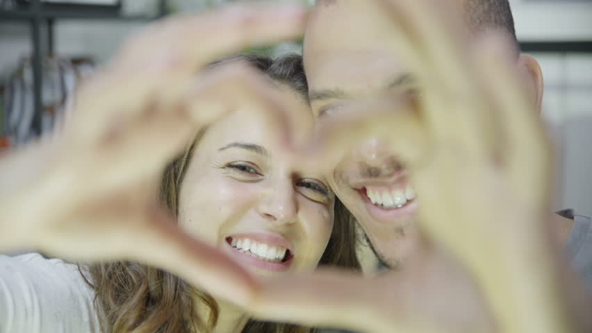 Close up of an attractive young mixed ethnicity couple who are laughing and making a heart shape with their hands. In slow motion. - HD stock video clip