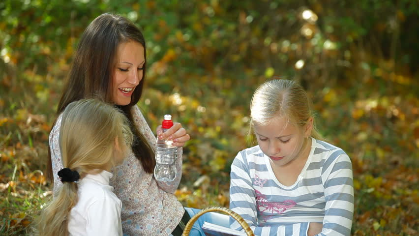 Young mother and two daughters enjoying autumn day at picnic in the park, children drinking water - HD stock video clip