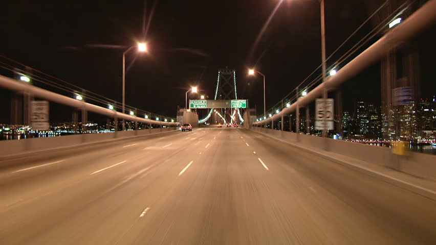 The lights of San Francisco twinkle in the night as this POV shot, crossing the