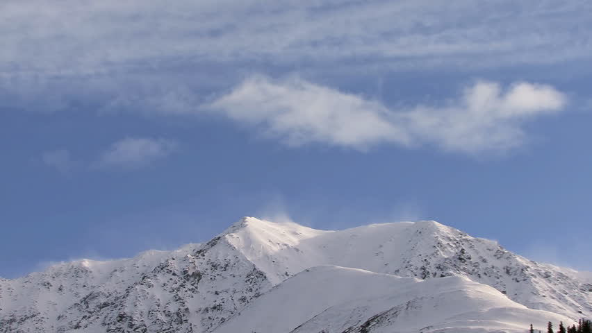 Stark, craggy mountains, with the air currents slamming into the other side forcing spindrift and billowing clouds to forma and dissipate over the mountain's edge. Time lapse. - HD stock footage clip