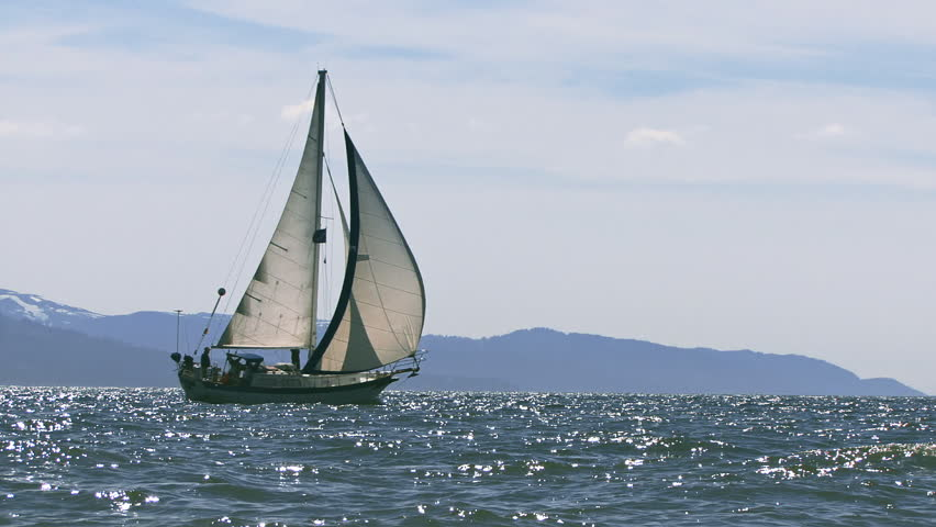 A sailboat, either cutter or masthead sloop, under way across the glistening