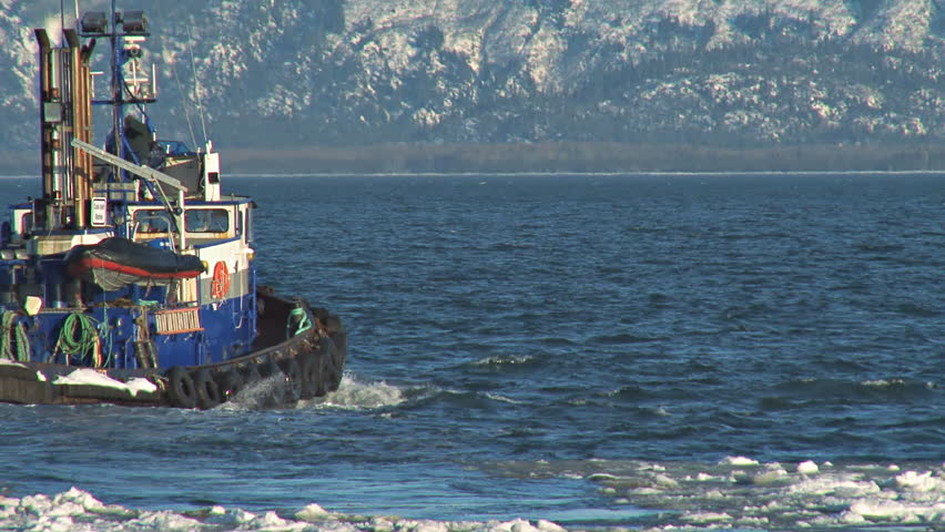 Pan/tracking shot of tugboat plowing through the icy waters as it leaves the Homer harbor.  - HD stock footage clip