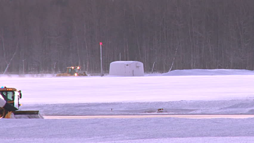 Long tight shot of a snow blower clearing snow from runway at Anchorage airport.