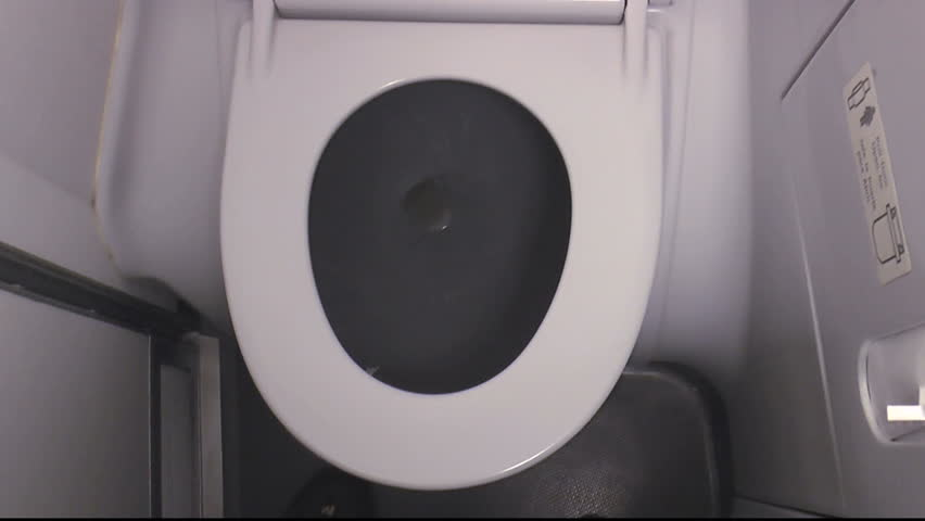 Airplane bathroom, pan from toilet to sink where hands turn on faucet, run water. 1080p