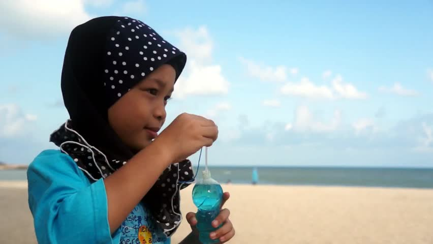 Beautiful muslim girl wearing scarf blowing bubbles at beach. profile with copyspace.