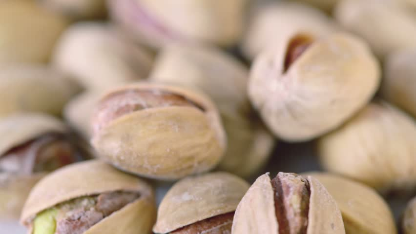 Handful of roasted salted appetizing pistachios spins closeup - HD stock footage clip