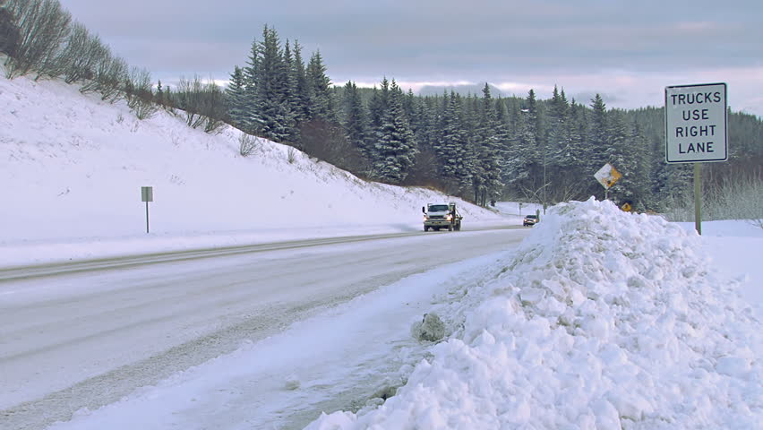 HOMER, AK - CIRCA 2012: Several vehicles being driven on a snowy Alaskan road in the winter time. Road signs show evidence of recent plow activity. - HD stock footage clip