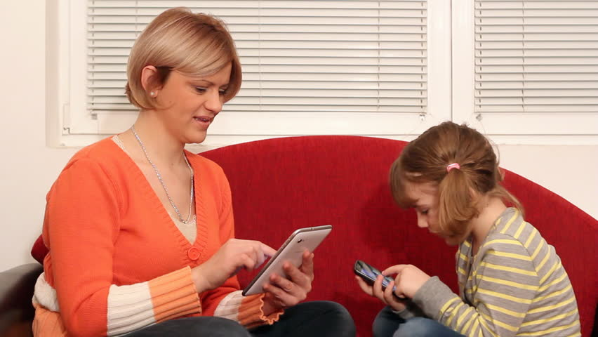 mother and daughter play with tablet and smart phone - HD stock footage clip