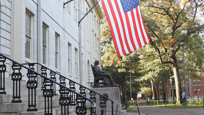 The American Flag Stars & Stripes Above The Statue Of John Harvard Outside Of University Hall In Harvard Yard At Harvard University, Cambridge Massachusetts