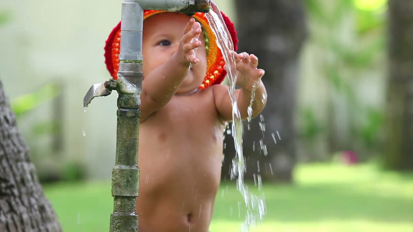 Cute small girl in hat playing with water