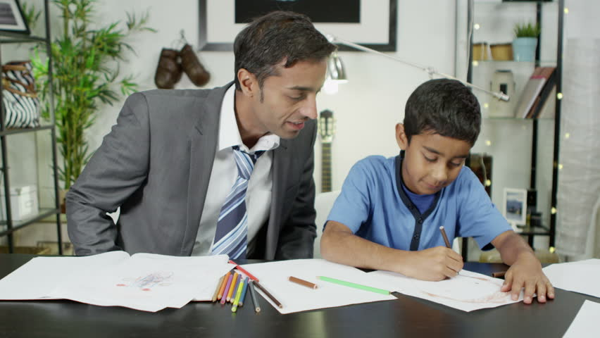A father helps his young son while the boy is doing his homework