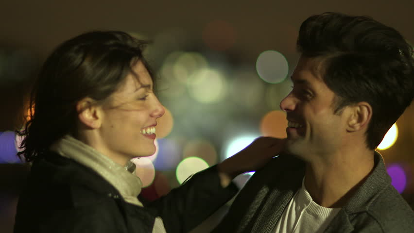 An attractive couple in love embrace and enjoy an intimate moment together, against the backdrop of city lights