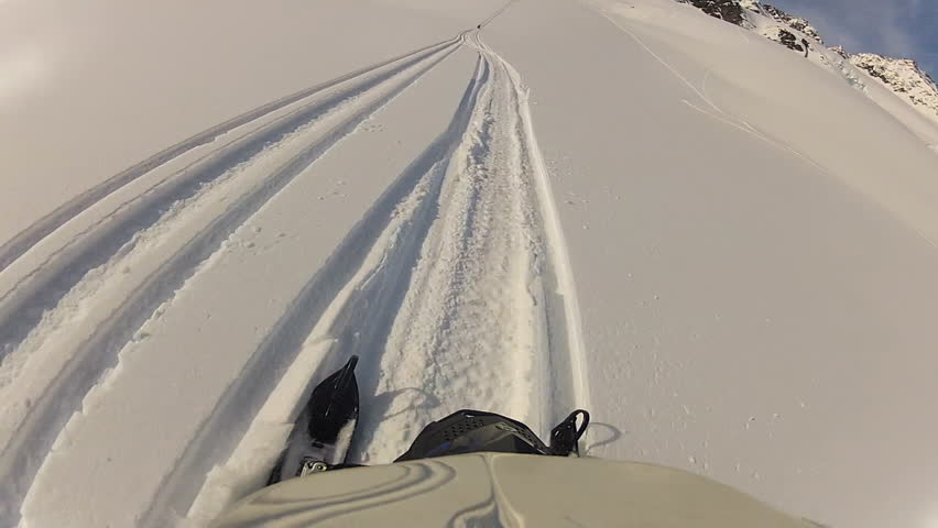 First person point of view shot of a snowmobile driving through fresh snow powder on the side of a mountain during the day.