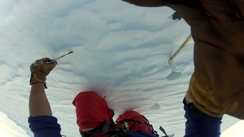 First person point of view shot of a man climbing up the side of a snow covered mountain during the day