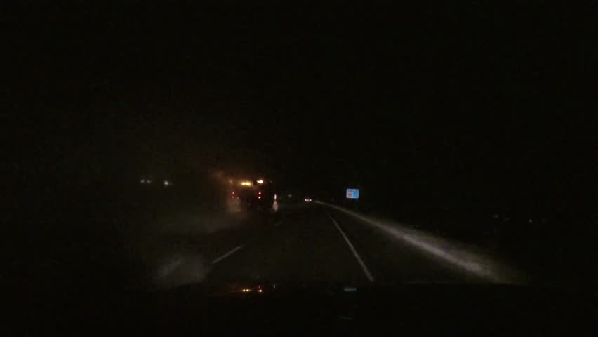 Night snow storm traffic plow driving POV. Winter snow blizzard with ice and snow on road. First person point of view (POV) looking through drivers windshield. - HD stock video clip