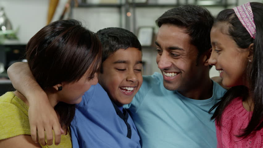 Happy family of 4 seated together at home. They are laughing and hugging. | Shutterstock HD Video #3204121