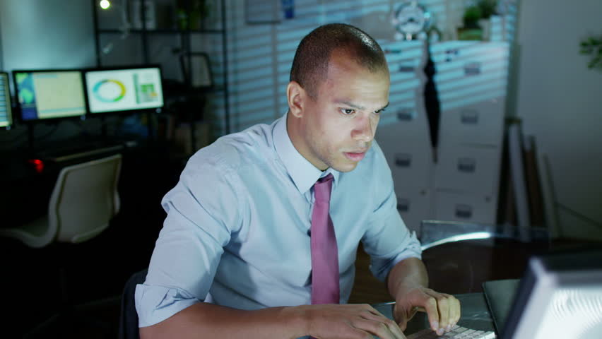 A young professional male is working late at night, a bank of computer screens can be seen in the background. He looks tired and uncomfortable and he loosens his tie - HD stock footage clip
