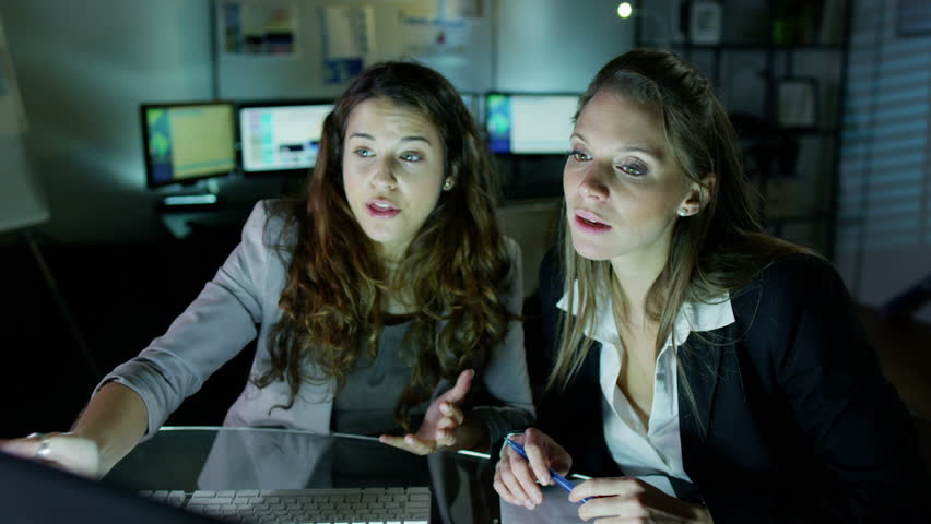 2 attractive female office workers are working late at night, a bank of computer screens can be seen in the background. Slow motion. - HD stock footage clip