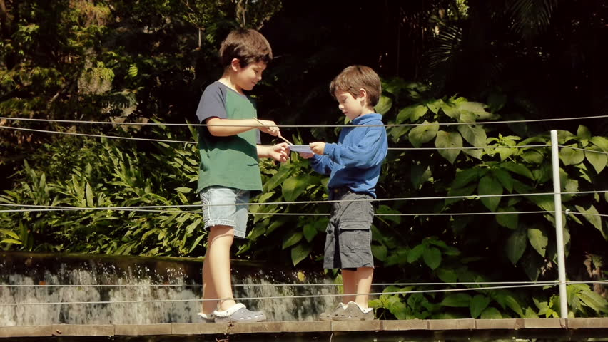 Hispanic Kids Blow Bubbles At Bridge over Water in Park. - HD stock footage clip