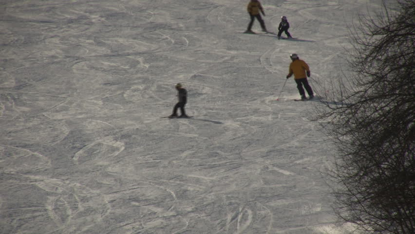 Winter scenic of a father and son skiing down hill on
