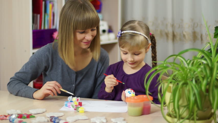 Mother and child decorate an Easter egg. Looking at camera - HD stock video clip