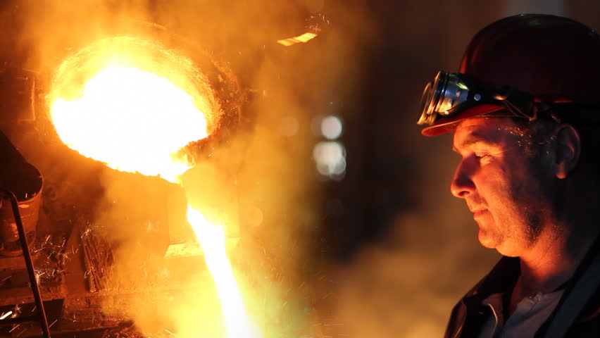 Hard work in the foundry, worker watching and controlling iron smelting in furnaces, too hot and smoky workplace. He puts on safety goggles - HD stock video clip