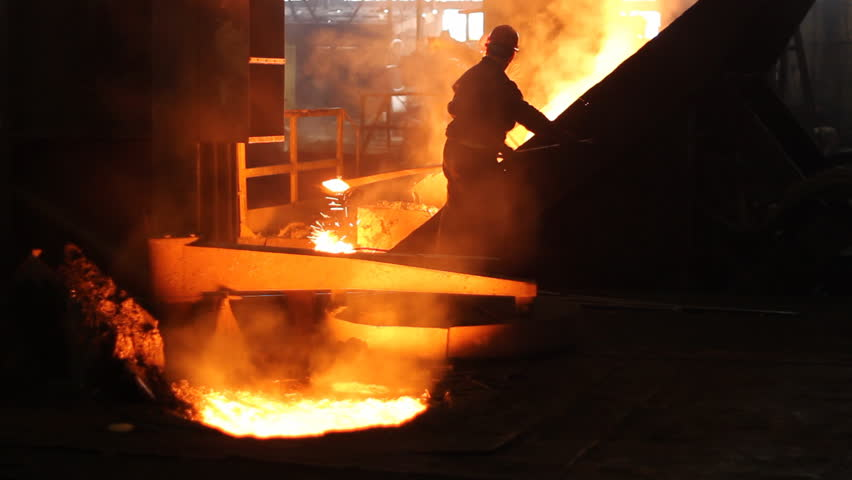 Hard work in the foundry, workers controlling iron smelting in furnaces, too hot and smoky working environment - HD stock footage clip