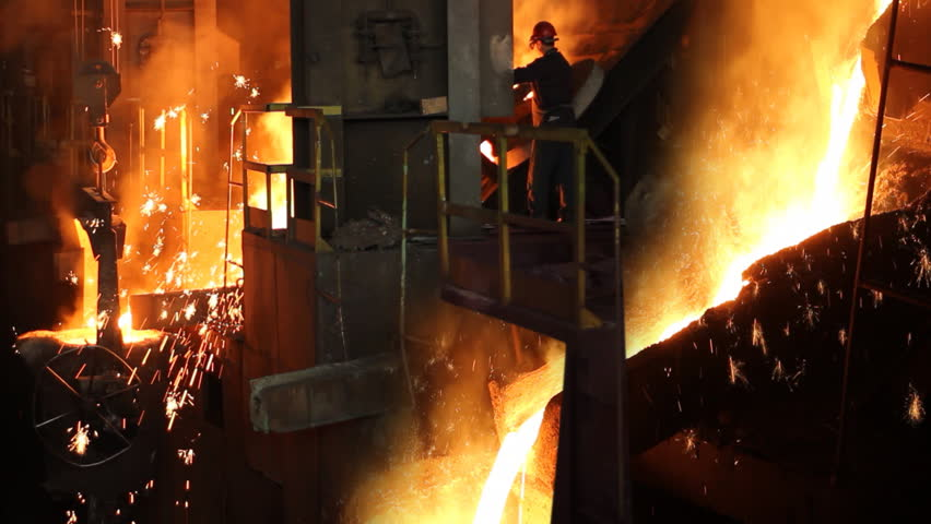 Hard work in the foundry, worker controlling iron smelting in furnaces, too hot and smoky working environment - HD stock video clip