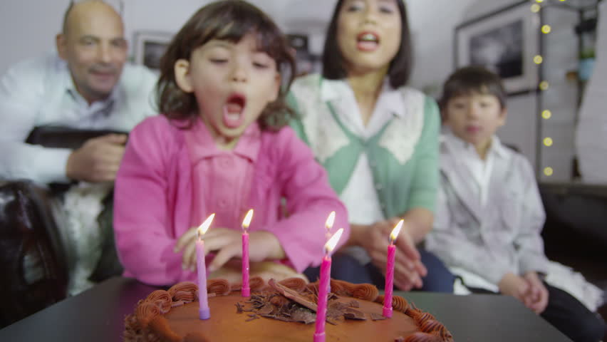 A cute little girl tries to blow out all the candles on her birthday cake but can't do it with just one breath. She gives a big smile and her family applaud her. In slow motion.