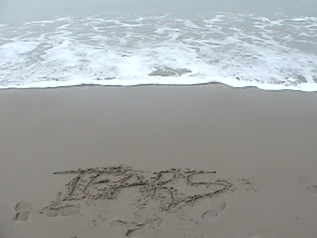 the word TEARS is washed away by the tide on the beach - SD stock footage clip