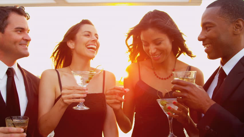 Smiling pretty diverse female and male friends enjoying cocktails and fun at city sunset party dressed in black shot on RED EPIC - HD stock footage clip