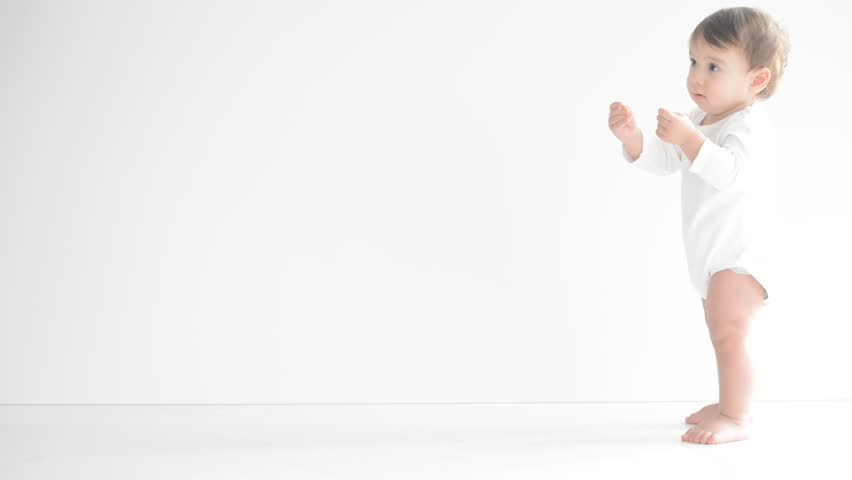 Happy little baby making first steps on white floor - HD stock video clip