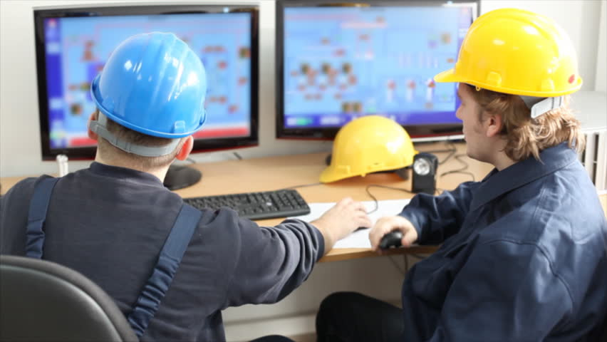 Two workers talking about a job in a factory, controls the operation of devices in a power plant