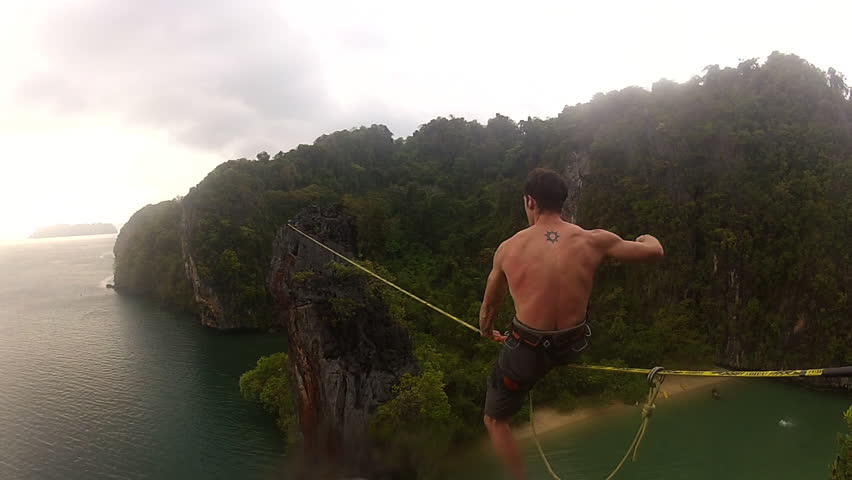 A climber crosses a slick line rope over the sea