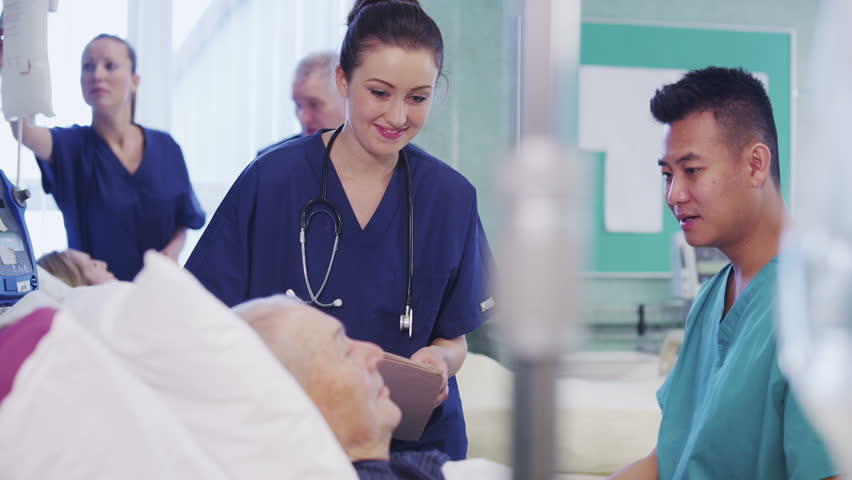 One male and one female nurse attend to an elderly male patient, checking his blood pressure and chatting with him. In the background a nurse and consultant specialist are discussing another patient. - HD stock footage clip