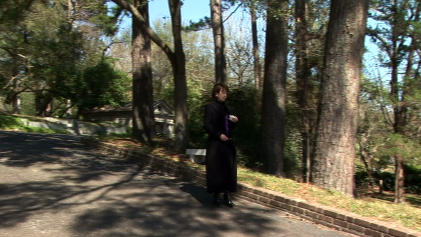 A sad woman walks past a section of graves in a large cemetery. - HD stock video clip